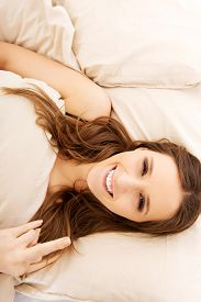 foto of middle finger  - Young happy woman showing middle finger in bedroom - JPG