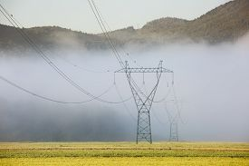 foto of electricity pylon  - Big electricity high voltage pylons with power lines on a green meadow in a foggy morning - JPG