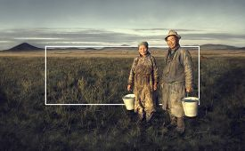 stock photo of mongolian  - Mongolian couple farmers holding basin and posing in the field - JPG