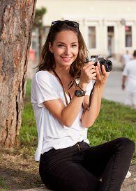 image of analogy  - Gorgeous young brunette woman using analog camera - JPG
