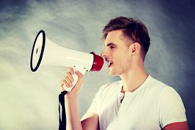 foto of shout  - Young handsome man shouting in megaphone - JPG
