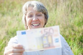 picture of fifties  - Old age woman holding fifty euro note - JPG