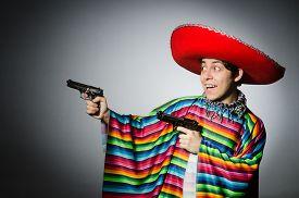 picture of handgun  - Man in vivid mexican poncho holding handgun against gray - JPG