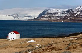 foto of iceland farm  - Quaint isolated farm house along the fjord westfjords surrounded by mountains covered in snow in Iceland - JPG