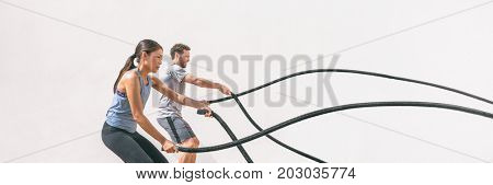 poster of Gym fitness sport fit couple working out battle rope exercise banner panorama. Woman and man cross t