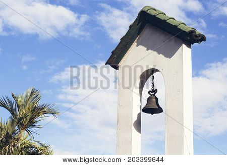 poster of Church bell on church tower on blue sky background. Catholic church building. Catholic religious architecture detail. White stone tower with bell. Traditional religious building on tropical island
