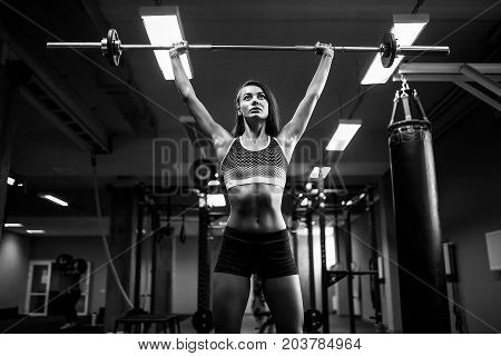 poster of Young fitness woman lifting a weight crossfit in the gym. Fitness woman deadlift barbell. Crossfit woman. Crossfit style. Crossfit and fitness