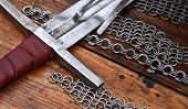 stock photo of arthurian  - Sword laying on a table a circuit and a chain armour - JPG