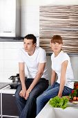 The young attractive couple sits at kitchen