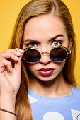 Surprised young woman in sunglasses over yellow background. Optics, sunglasses.  poster