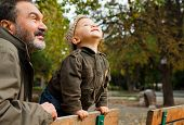 Grandfather and child leaning on bench in the park on autumn day, looking up