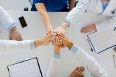 medicine, healthcare and teamwork concept - group of doctors with cardiograms making high five at ho poster