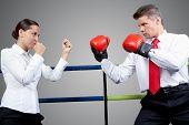 Porträt von aggressiven Geschäftsmann in Boxhandschuhe und Ernst Frau miteinander in Konflikt