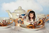 Tea party with antique tea cups and a miniature girl like in alice in wonderland