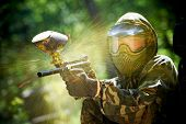 paintball sport player wearing protective mask aiming gun and shotted down with paint splash in summ