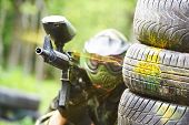 paintball sport player wearing protective mask aiming gun from shelter under gunfire attack with paint splash
