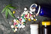Marijuana Leaf With Medical Pills On Dark Fabric poster