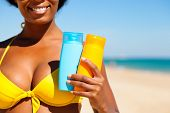 Woman in yellow bikini offering suncream on the beach in order to avoid sunburn, FOCUS is on hand, l
