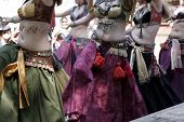 image of unclothed  - women in colorful attire belly dancing - JPG