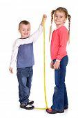 little boy measuring her sister's height