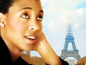 Young African woman in business suit dreaming about Paris ? Eiffel tower in the background