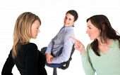 Neatly dressed brunette pointing accusing finger at a blond woman with a smiling man on a chair in t
