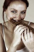 Beautiful red hair woman eating a slab of chocolate with it all over her face