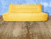Illustration of yellow couch on wooden floor against grunge blue wall