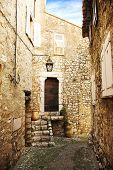Romantic narrow cobble street with sandstone houses in a village of Saint Paul de Vence, France
