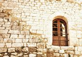 Grunge sandstone wall with a wooden arch window in a French village of Saint Paul de Vence