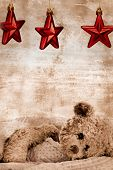 teddy bear in blanket under three Christmas red stars on grunge background with copy space - generic