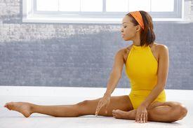 stock photo of ballet dancer  - Ballet dancer concentrating on stretching on floor of art training room - JPG