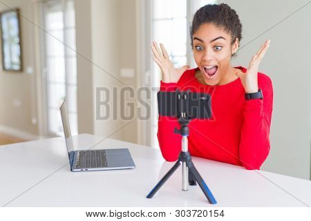 poster of Young african american woman doing video call using smartphone camera celebrating crazy and amazed f