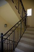 stock photo of bannister  - A stair well with wrought iron bannister - JPG