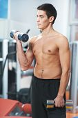 Young athlete man at biceps brachii muscles exercises with training dumbbells in fitness gym
