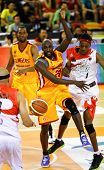 KUALA LUMPUR - FEBRUARY 19: Singapore Slingers (yellow) and Malaysian Dragons players go for the loose ball at an ASEAN Basketball League match on February 19, 2012 in Kuala Lumpur, Malaysia.  Dragons won 86-71.