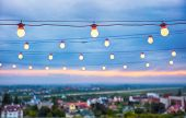 Several Rows Of Decorative Outdoor Light Strings Hanging On Cityscape Background At Twilight poster