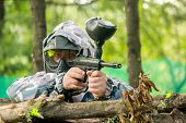 A Paintball Player Who Is Ready To Shoot From Hiding. Lying On The Ground And Shooting.  Immediately poster
