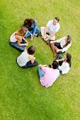 Group of friends sitting in a circle and talking - outdoors
