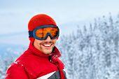 Joven esquiadora masculino contra la montaña, orientación horizontal