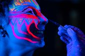 Ultraviolet Black Light Glowing Bodyart Processing On Young Womans Face. Pink And Purple Dyes In Col poster