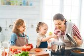 Healthy food at home. Happy family in the kitchen. Mother and child daughter are preparing proper me poster