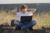 Resto adolescente con Laptop Mantenga las manos detrás de su cabeza