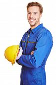 Happy smiling construction worker with yellow hardhat in blue overall