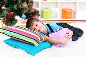 Little boy lying on pillows with gift in his hands under Christmas Tree waiting for Santa Claus to c