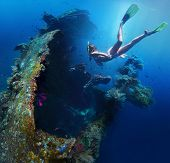 Underwater shoot of a woman exploring USAT Liberty wreck on a breath hold. Tulamben, Bali island, In