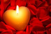 A heart shape candle surrounded by red rose petals covered in water droplets, a good image for a Valentines day or other romance related theme.