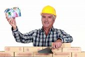 Tradesman holding up a house model make out of money