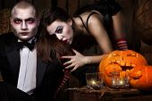 Portrait of a man and sexy woman vampires with halloween pumpkin against wooden background. Shot in