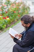 POCHAYIV, UKRAINE - AUGUST 14: Unidentified orthodox priest reading a book in Holy Dormition Pochayi